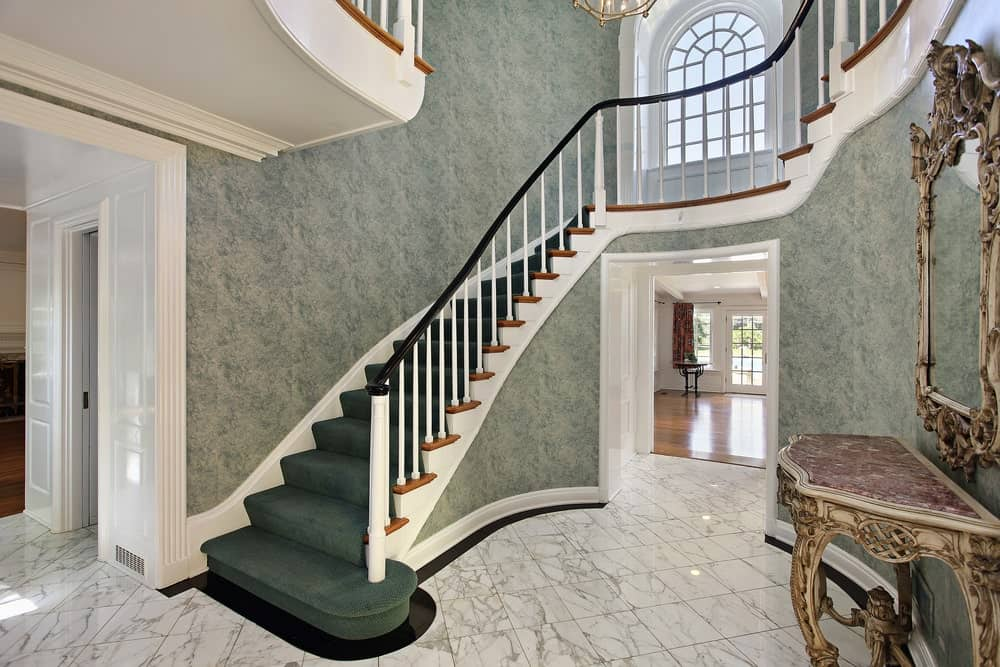 A stunning staircase featuring classy walls and handsome green carpet floors lighted by a gorgeous chandelier hanging from the high ceiling.