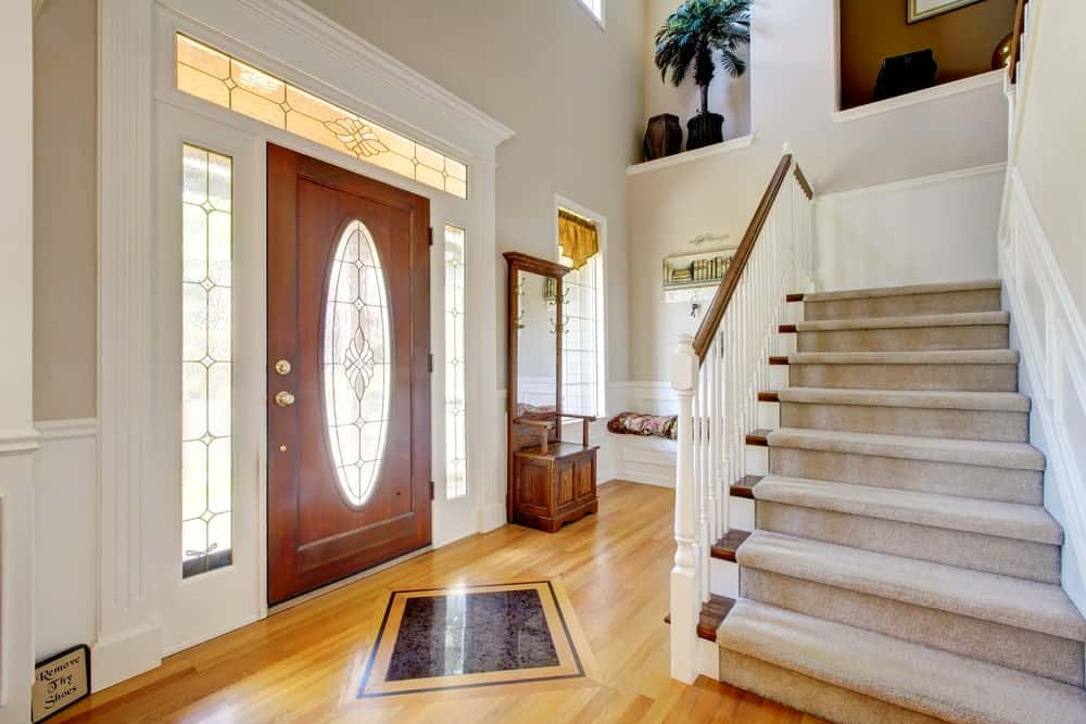A small home entry with a staircase with carpet floors and white railings.