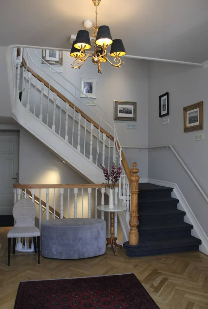 This home boasts a staircase with elegant blue carpet floors and light gray walls.