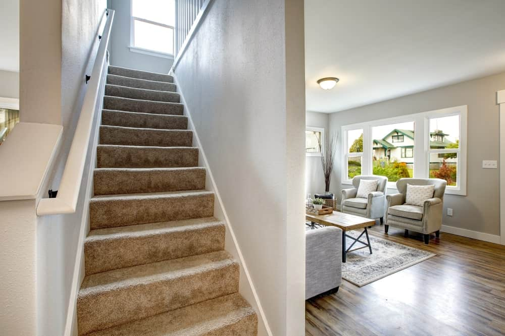 A straight staircase with floors covered with classy carpet. It also features a charming white handrail.