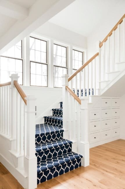 This staircase features stylish carpet floors and white walls, along with white railings and wooden handrails.