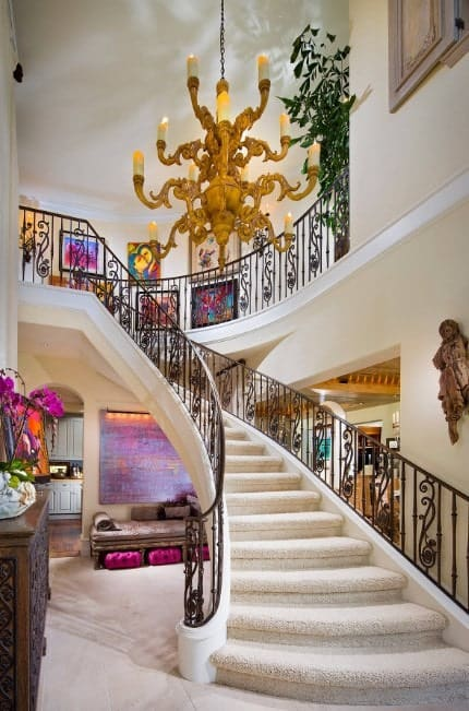 This home boasts a glamorous staircase with white carpet floors and lighted by a stunning chandelier.