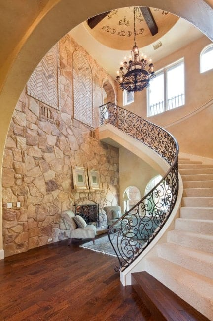 This home boasts a magnificent staircase with white carpet floors and stylish iron railings lighted by a glamorous chandelier.