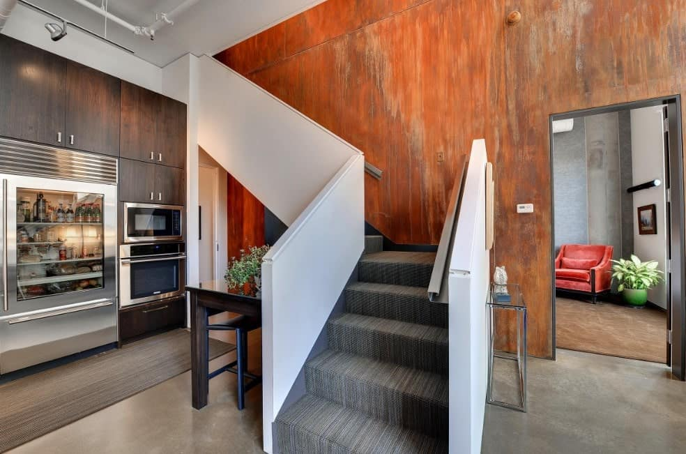 A modish L-shaped staircase with stylish gray carpet floors and steel handrails.