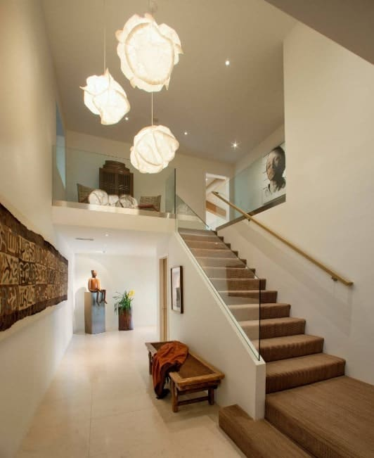 A modern house featuring an L-shape staircase with brown carpet floors and glass railings, lighted by a gorgeous pendant lighting.