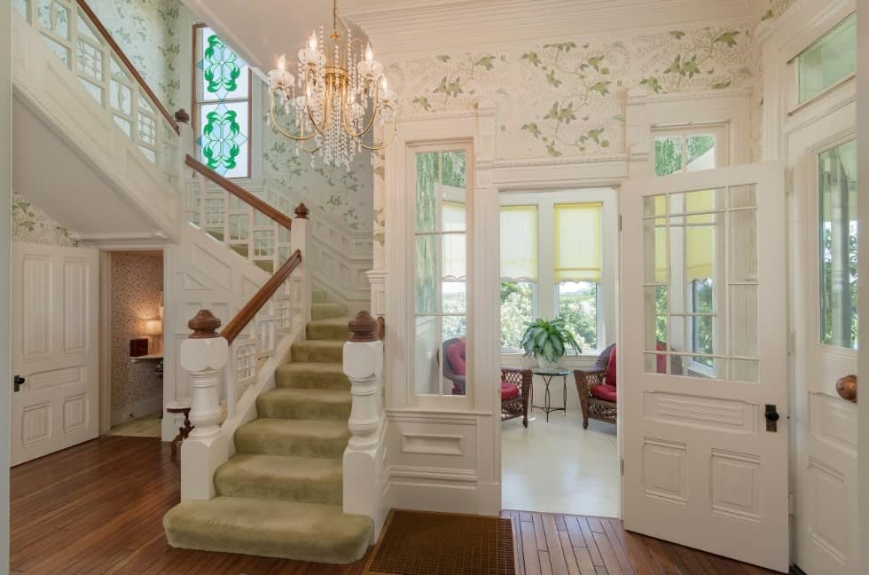 This home features a small staircase with carpet floors and white railings, lighted by a gorgeous chandelier.