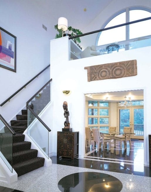 A modern home with a stylish staircase featuring stylish black carpet floors and glass railings.