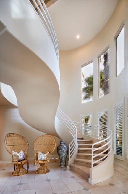 This home boasts a stunning staircase with brown carpet floors and white railings.