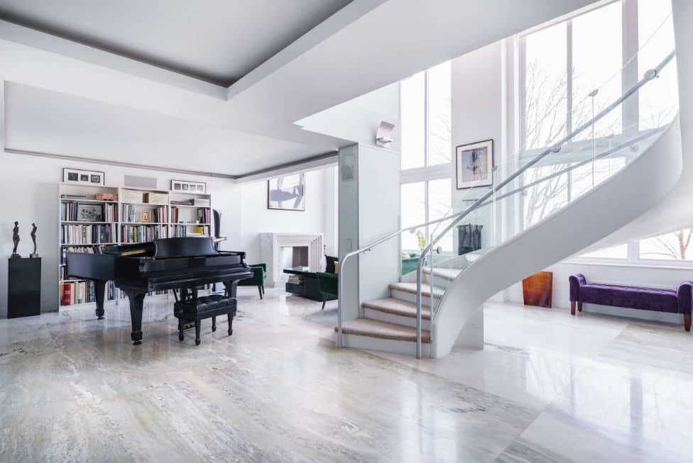 Large formal living space with a cozy sofa set near the fireplace, a large bookshelf near the grand piano and a stunning staircase with carpet floors and glass railings.