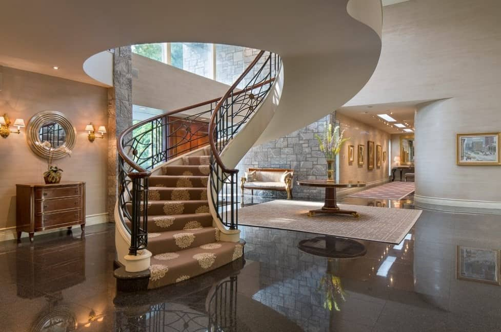 This home's foyer boasts a circular staircase with classy carpet floors and iron railings.