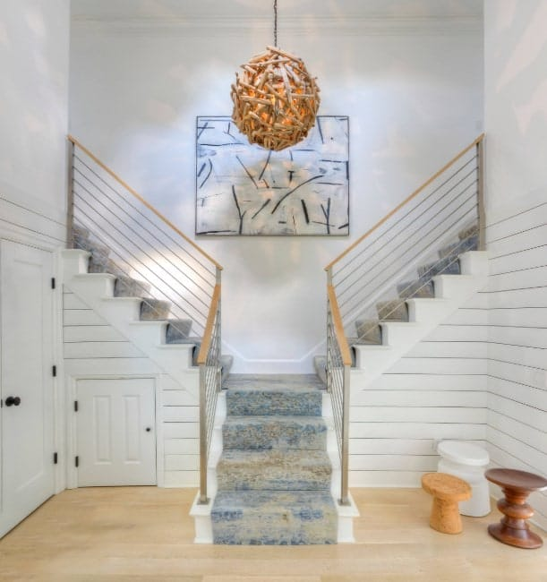 A split staircase with charming carpet floors and steel railings. There's an attractive wall decor on the middle as well.