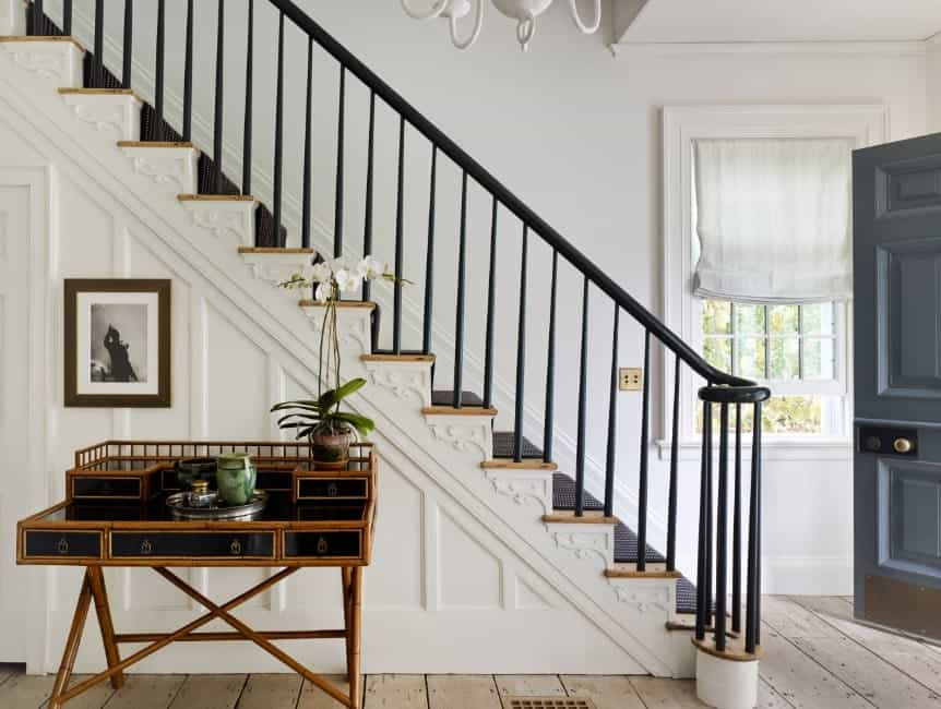 A straight staircase with black iron railings and elegant black carpet floors.