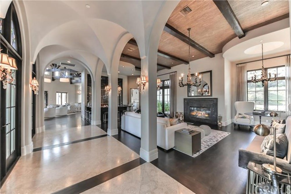 This celebrity living room has a hallway of groin vault ceilings leading to the living room area. This has a tall wooden ceiling that has dark wooden exposed beams that match the dark hardwood flooring and the dark mantle of the fireplace contrasted by the large white sofa.