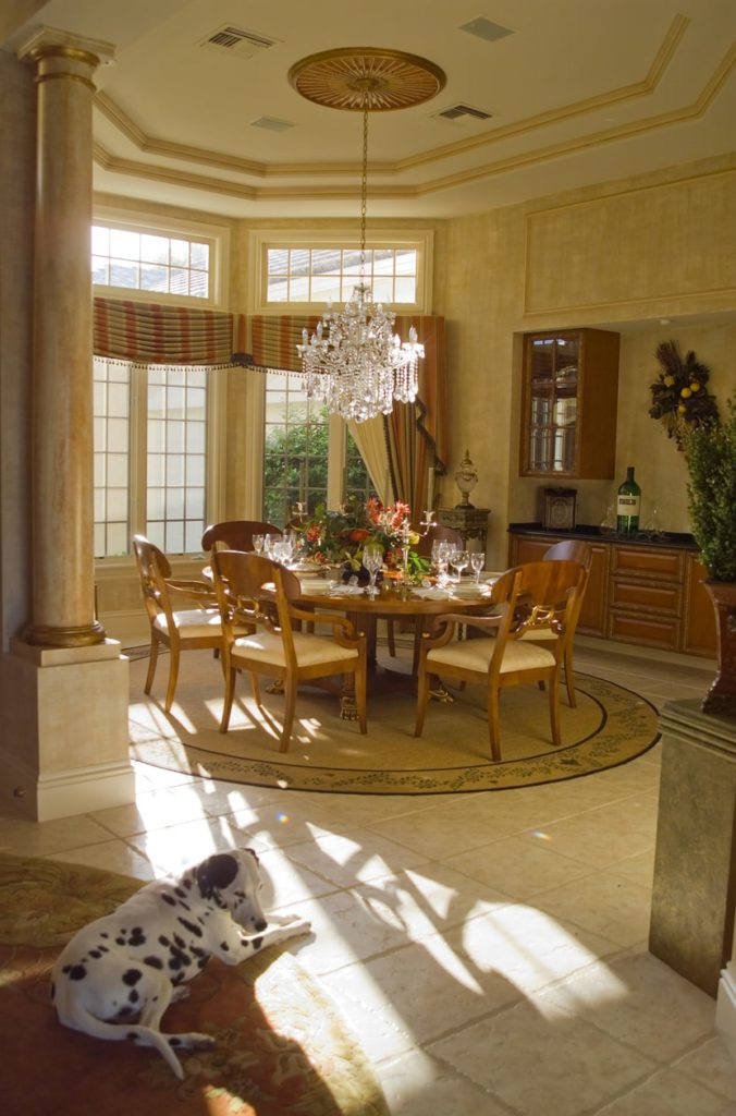 A round dining table set lighted by a glamorous chandelier set on the home's tall tray ceiling.