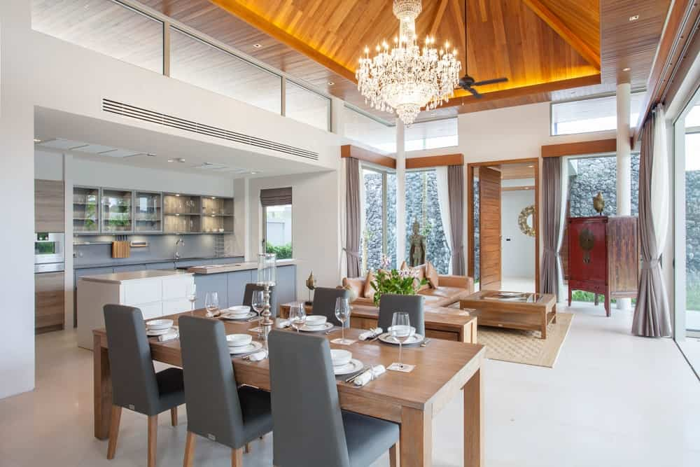 A great room featuring a living space, a dining table set and a kitchen. The home features white floors and a high ceiling.