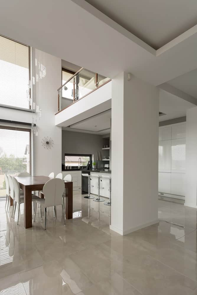 Modern home with a dine-in kitchen surrounded by tiles floors and white walls, along with a high ceiling.