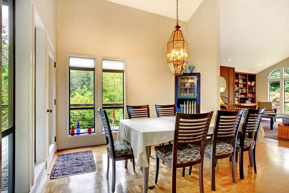 A dining room set on stylish floors and is surrounded by beige walls, lighted by a charming chandelier set on the home's high ceiling.