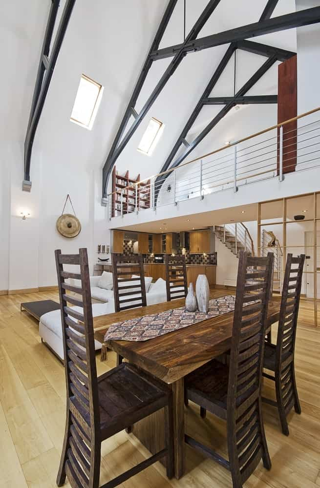 A rustic dining table set with a stylish set of high back chairs. The area is situated on the home's hardwood floors and under the high ceiling.