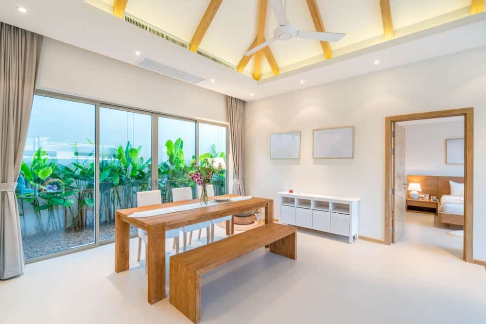 Spacious dining area featuring white carpet floors and white walls, along with a stunning high ceiling with exposed beams.