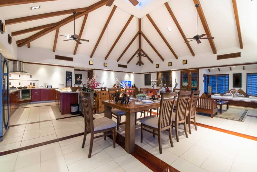 Large great room featuring a rustic dining table set situated on the home's stylish floors and under the high ceiling with beams.