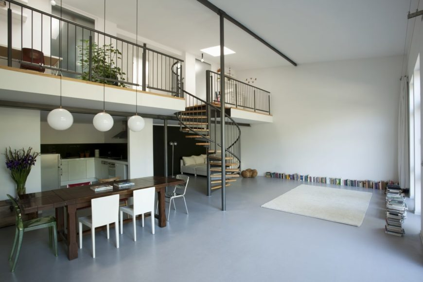 A spacious dining area featuring a stylish dining table set lighted by pendant lights hanging from the tall ceiling.