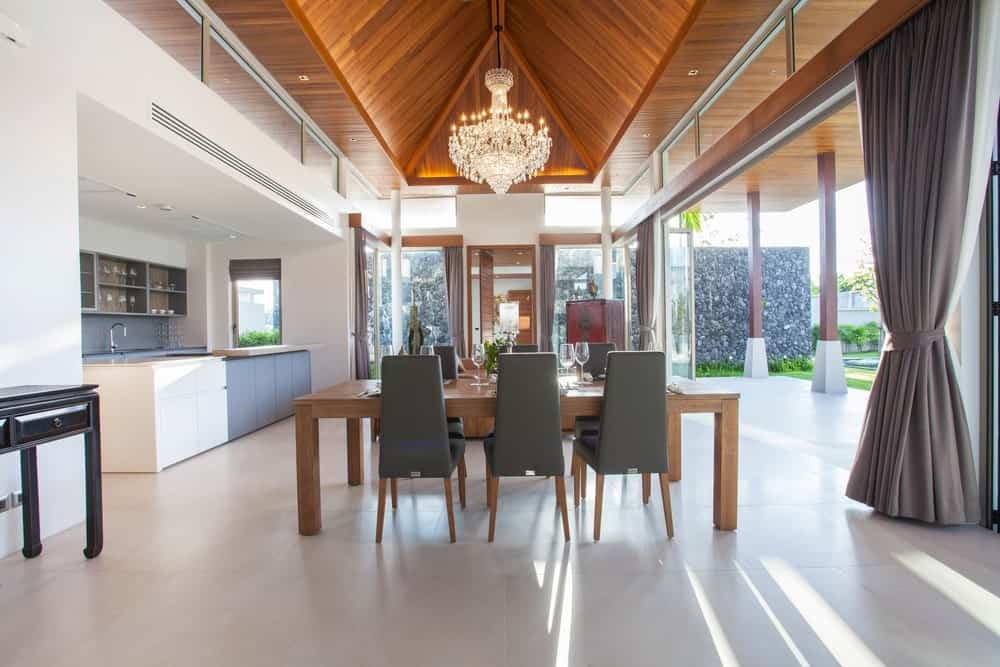 Large dining area lighted by a glamorous chandelier set on a stunning ceiling.
