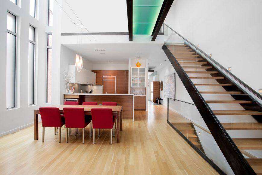 A modern home with a dine-in kitchen. It features a wooden dining table set with red chairs, lighted by charming pendant lights.