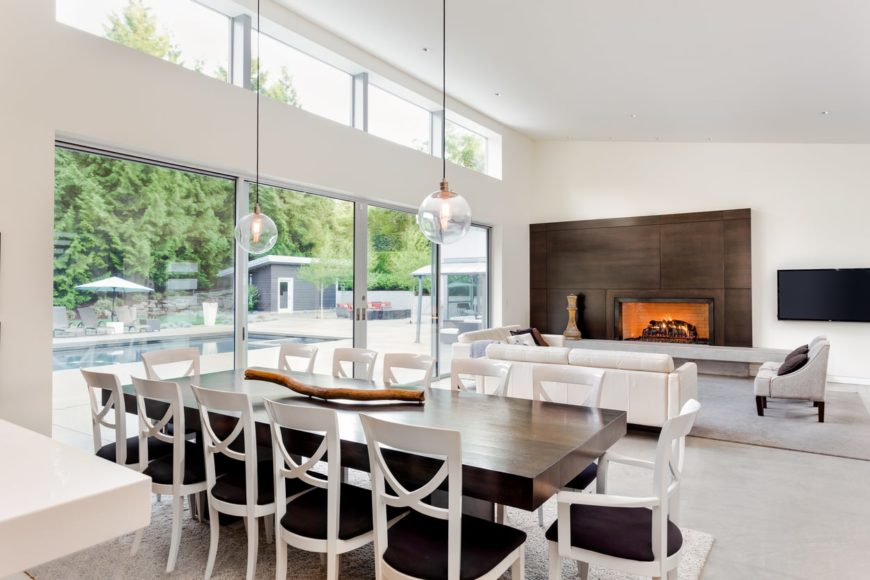 A dining table set for 12, placed on the home's great room. It features a modern table and chairs set, along with classy pendant lights hanging from the home's tall ceiling.