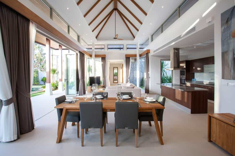 A great room with a nice living set, a modish kitchen and a classy dining table set under the stunning tall ceiling.