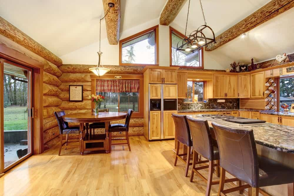 A dine-in kitchen featuring a round dining nook and a breakfast bar set on the hardwood floors, matching the wooden cabinetry and kitchen counters.