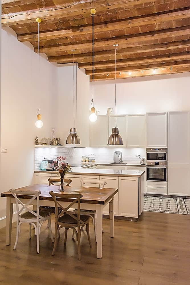 A dine-in kitchen featuring a square dining table set lighted by pendant lights hanging from the tall ceiling with exposed beams.