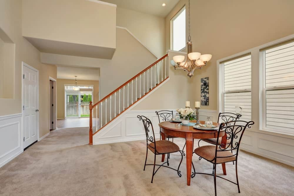 A round dining table set situated on the home's carpet floors and is lighted by a gorgeous chandelier.