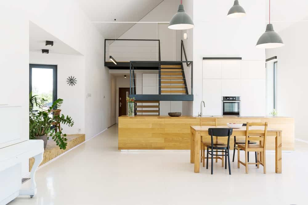 Modern house with a dine-in kitchen. It features a wooden counter and a wooden dining table set. The room features white floors and high ceiling, lighted by pendant lights.