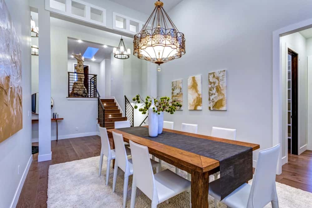 A modern home with a nicely set dining area featuring multiple artistic wall decors and stunning ceiling light.