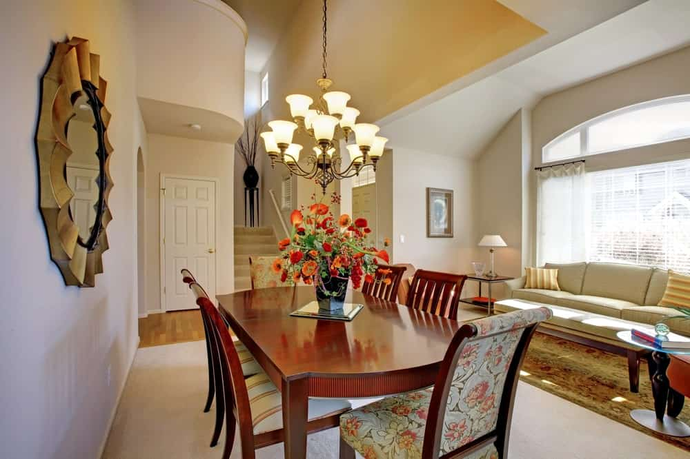 A classy dining table set lighted by a beautiful chandelier hanging from the home's high ceiling.