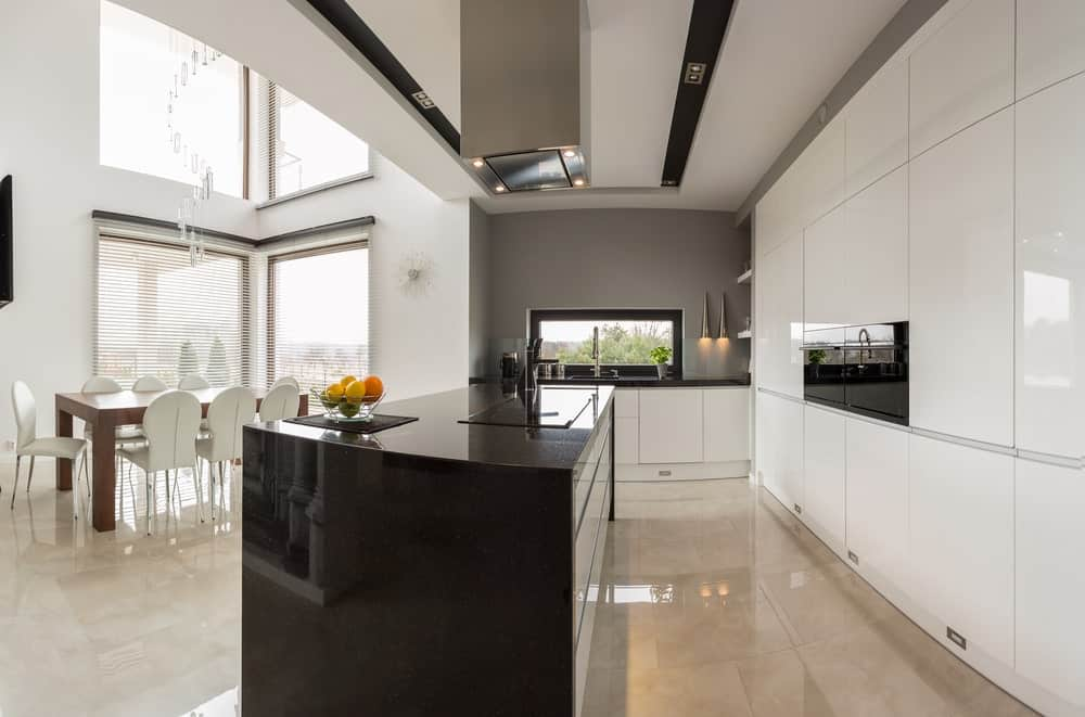 Modern home with a stylish center island and a dining table set for 8, situated on the home's tiles floors and under the high ceiling.