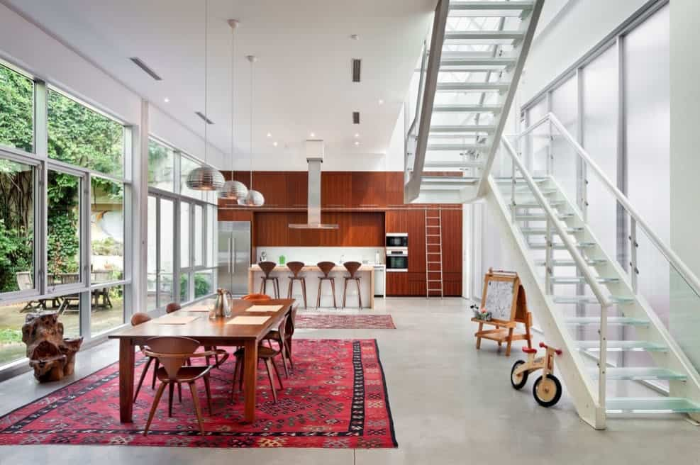 A large dining area set on a fabulous red rug and is lighted by a set of pendant lights hanging from the tall ceiling.