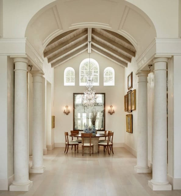 Large dining hall featuring a round dining table set lighted by wall lights and a glamorous chandelier hanging from the tall vaulted ceiling.