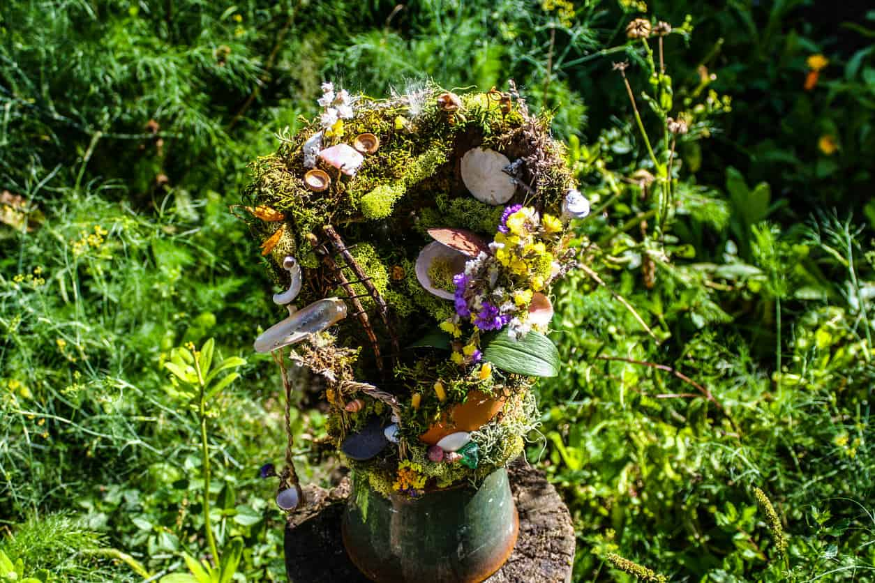 Elaborate vertical fairy garden in pottery mug placed on stump.