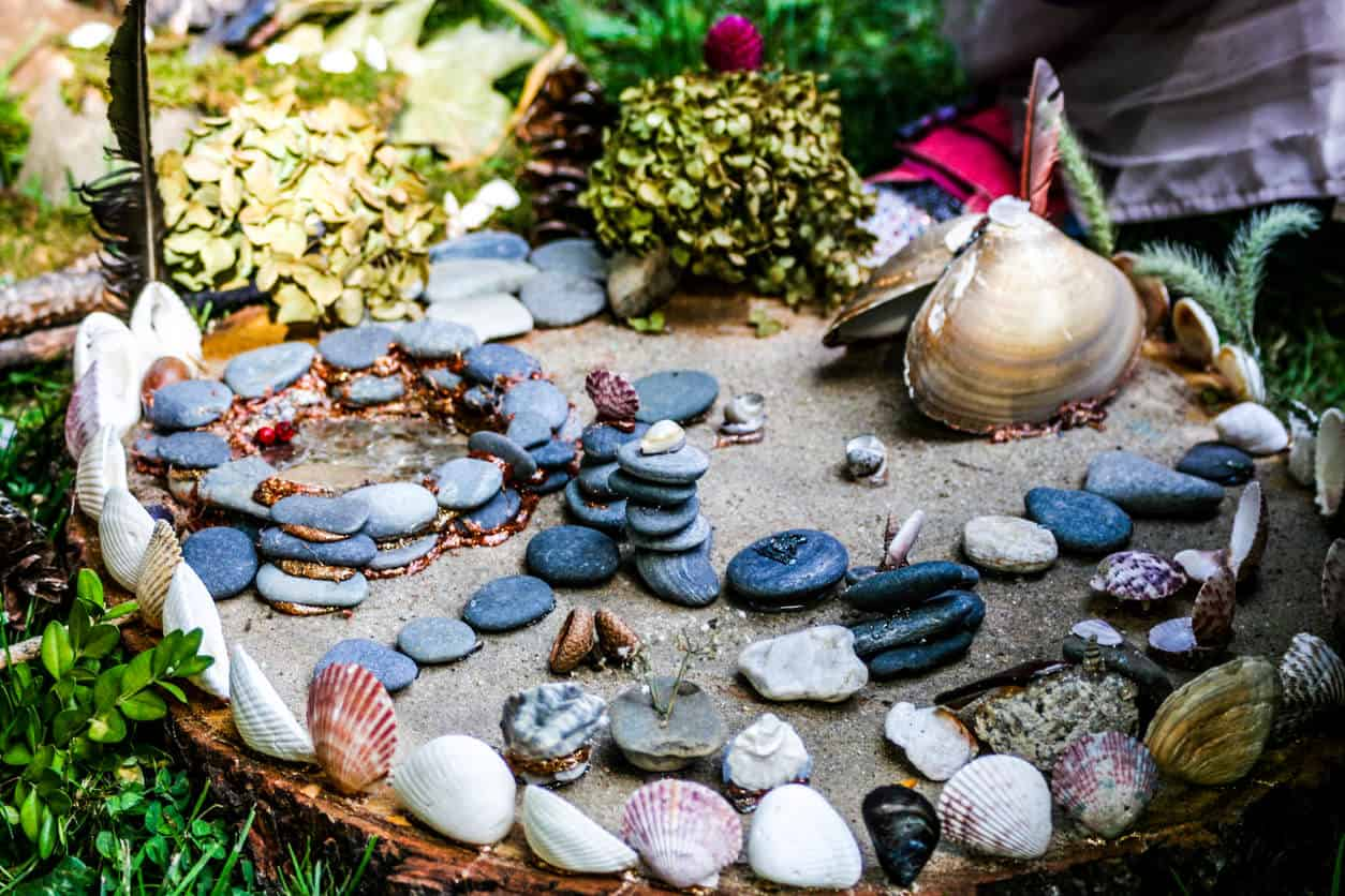 An open concept fairy house built with pebbles and shells.