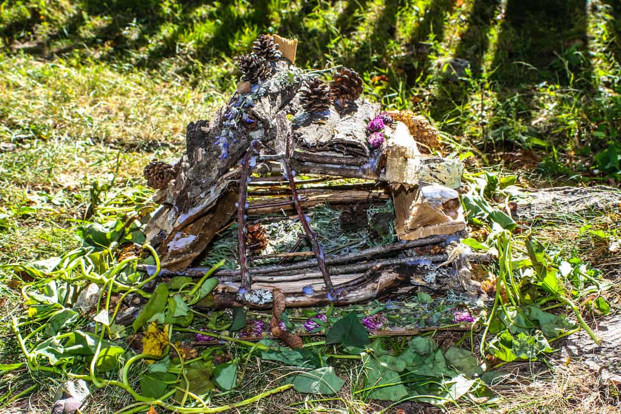 A spacious fairy house built with sticks and logs and includes pine cones for decoration.