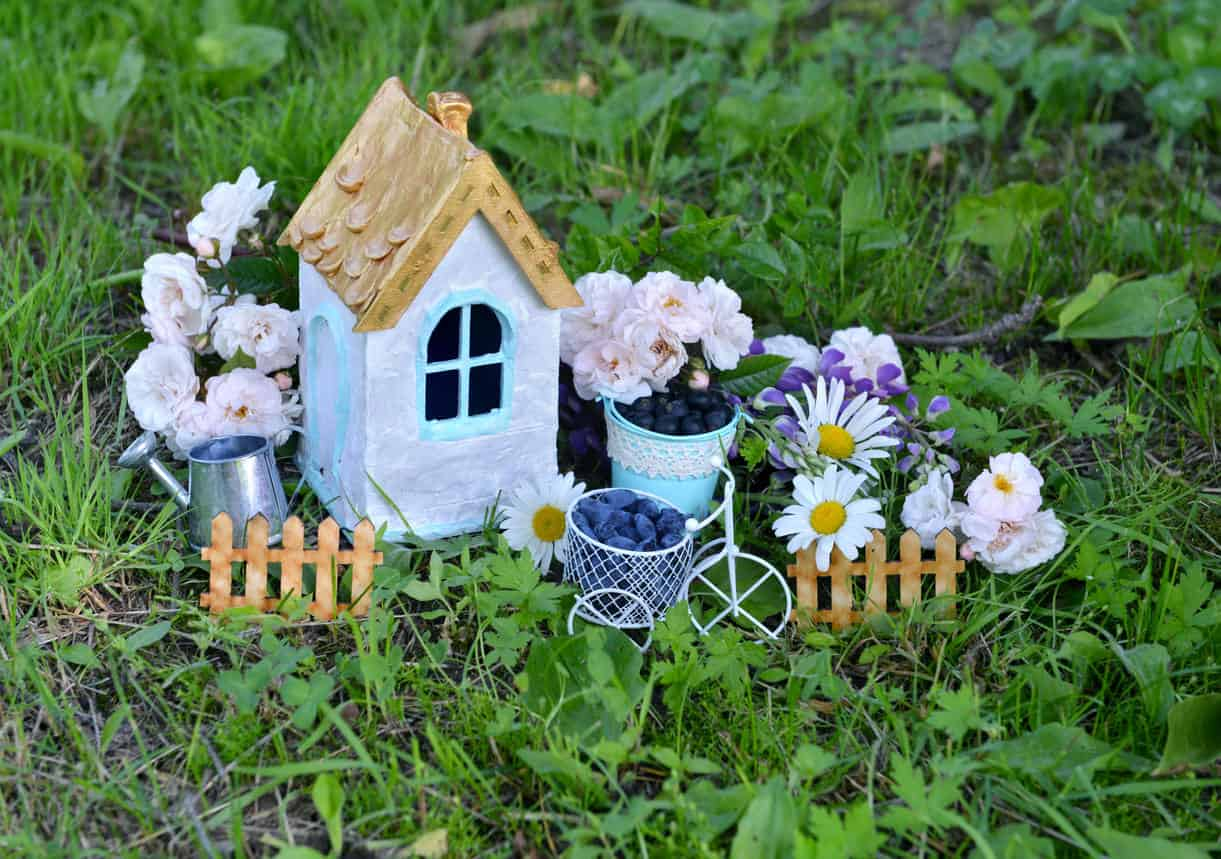 Lovely miniature houses and flowers with picket fence in garden.