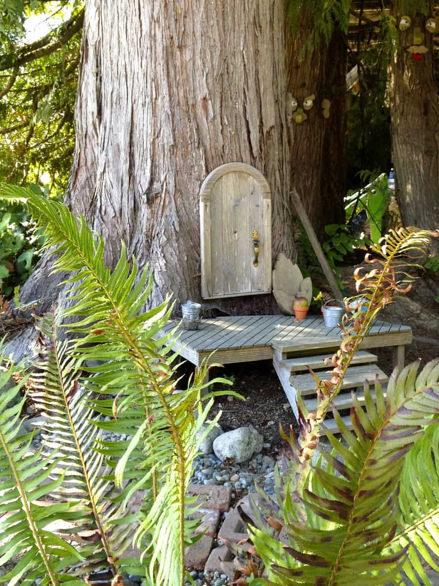 Gnome door in tree with front porch and stairs in the forest.