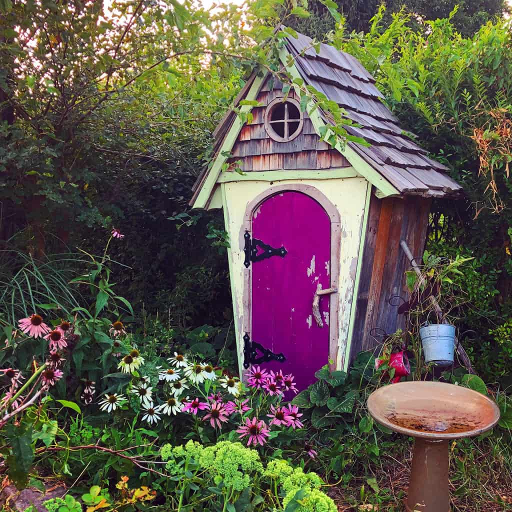 Tiny, purple fairy house in the woods.