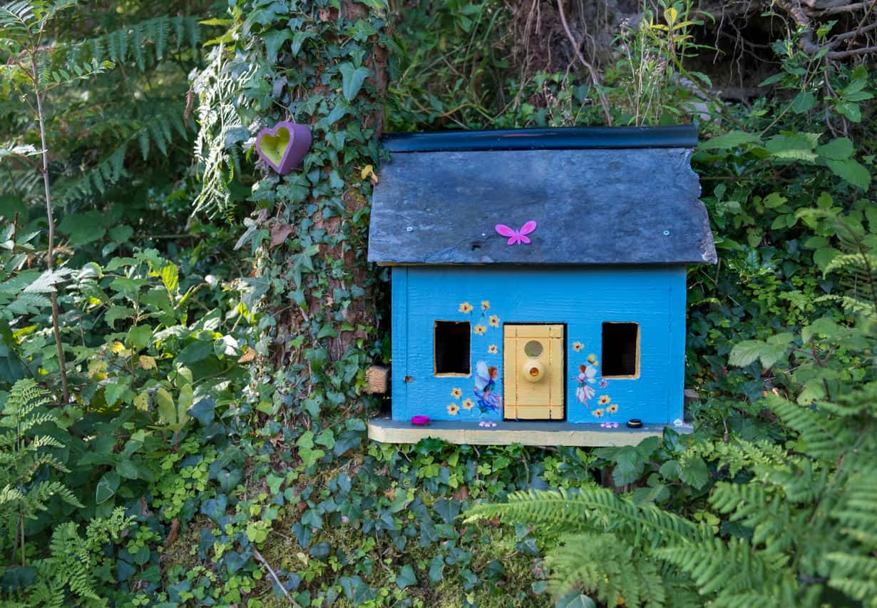 Blue Fairy house along the path on the coast of Ireland. House is blue with yellow door, in a green lush forest.