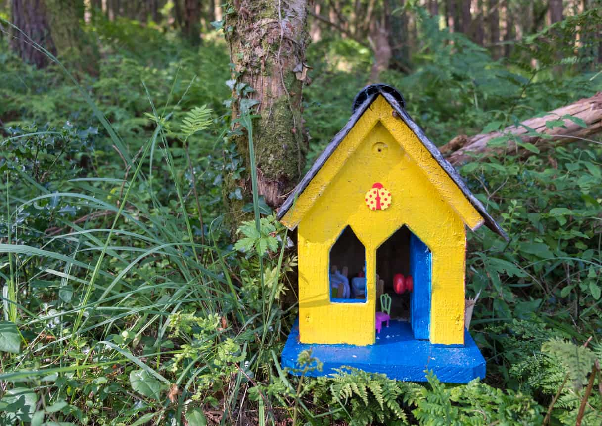 Yellow Fairy house along the path on the coast of Ireland. House is yellow with blue door, in a green lush forest.