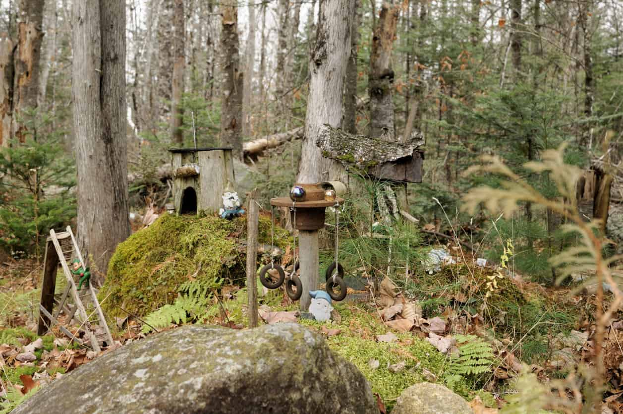 A fairy garden in the woods with playground, houses, ladders - an entire fairy village.