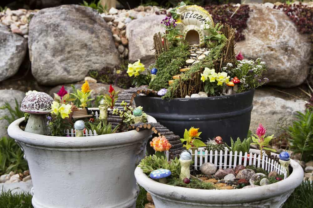 Incredible fairy garden in a series of three large flower pots all connected with miniature log bridges set in garden.