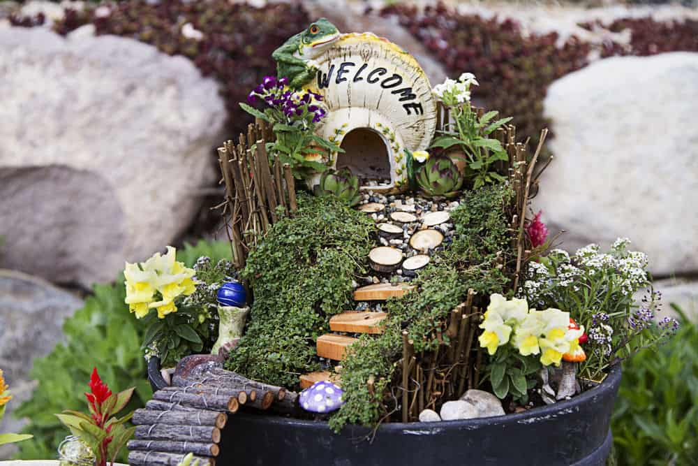 Flower pot with detailed fairy garden that includes a small fairy house, walkway decorated with flowers.