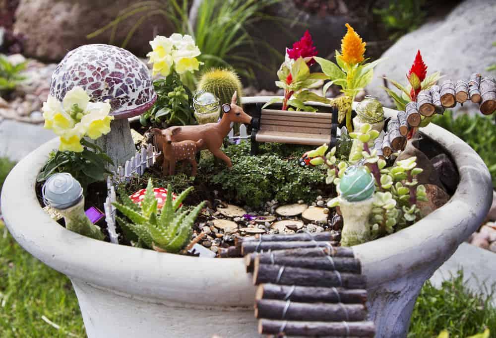 Close-up of fairy garden in a large planter pot. Includes mushroom, deer, flowers and mini log bridge to adjacent fairy garden pots.